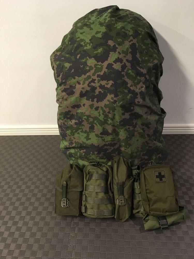 Rinkka pakattuna ja varustettuna M05 sadesuojalla. Etualalla taisteluliivi.