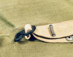 Weave the folded strap through one or both slots. Use a piece of Paracord inside the loop to prevent the strap from slipping back.